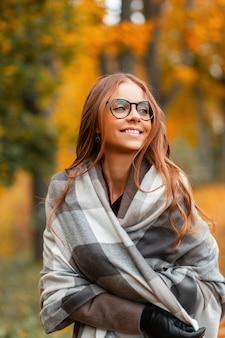 Gelukkig jonge hipster vrouw met een positieve glimlach in een stijlvolle gebreide sjaal in een jas in trendy glazen wandelingen in het najaar park. blij meisje in modieuze bovenkleding geniet van een wandeling door het bos.