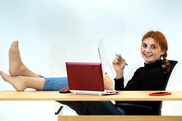 Gelukkig jonge kantoor werknemer vrouw zitten ontspannen met voeten op tafel achter bureau met laptop, mobiele telefoon en notebook