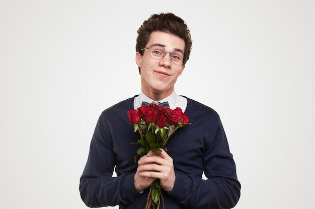 Gelukkig jonge kerel in elegante slijtage en glazen met boeket van rode rozen in handen glimlachen en kijken