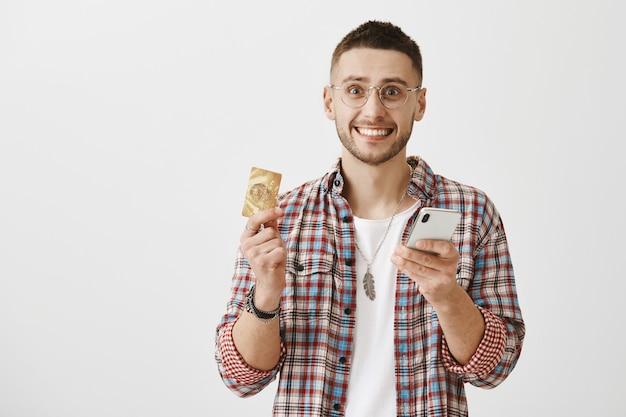 Gelukkig jonge kerel met een bril poseren met zijn telefoon en kaart