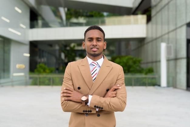 Gelukkig jonge knappe afrikaanse zakenman lachend met armen gekruist in de stad