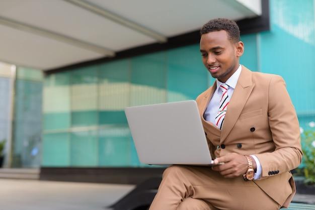Gelukkig jonge knappe afrikaanse zakenman met laptop zittend in de stad buiten
