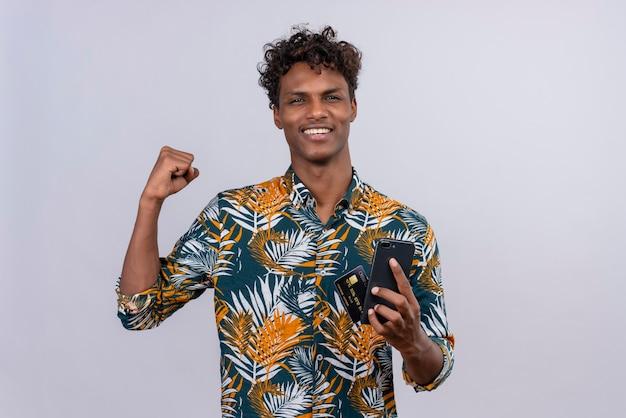 Gelukkig jonge knappe donkerhuidige man met krullend haar in bladeren bedrukt overhemd met smartphone en creditcard met gebalde vuist