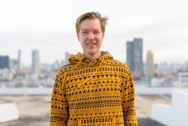 Gelukkig jonge knappe man dragen hoodie tegen uitzicht over de stad
