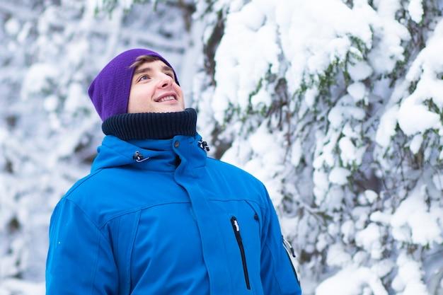 Gelukkig jonge knappe man in warme kleren en hoed genieten van een goede dag