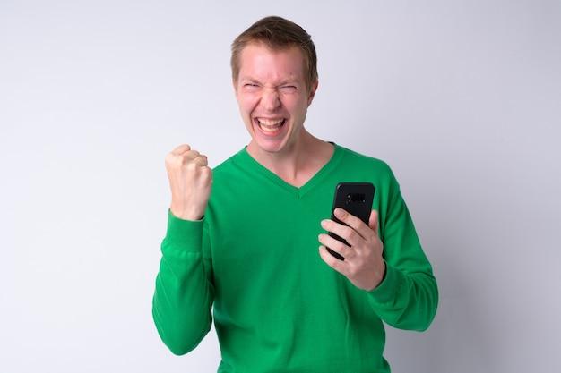 Gelukkig jonge knappe man met behulp van telefoon en goed nieuws krijgen