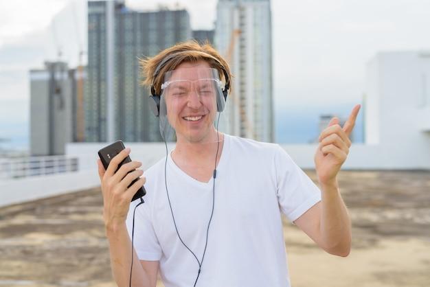 Gelukkig jonge knappe man met gezicht schild dansen terwijl u luistert naar muziek op het dak van het gebouw