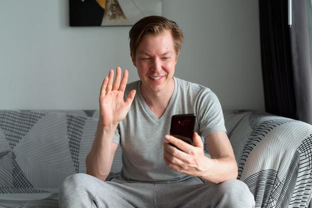 Gelukkig jonge knappe man videobellen met telefoon thuis