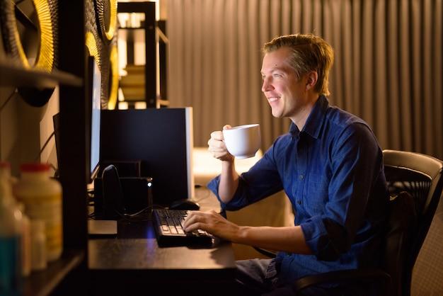 Gelukkig jonge knappe zakenman koffie drinken terwijl thuis overuren
