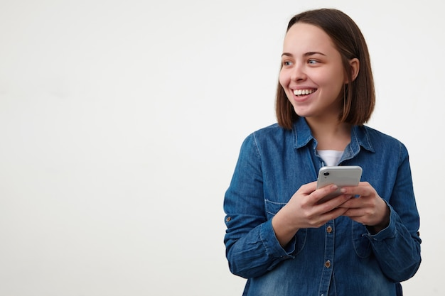 Gelukkig jonge kortharige brunette vrouw met casual kapsel houdt haar smartphone vast en glimlacht wijd terwijl ze opzij kijkt, geïsoleerd op witte achtergrond