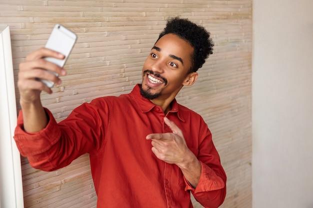 Gelukkig jonge kortharige krullende brunette man met donkere huid zijn hand omhoog houden tijdens het maken van selfie en ponting, poseren op beige interieur