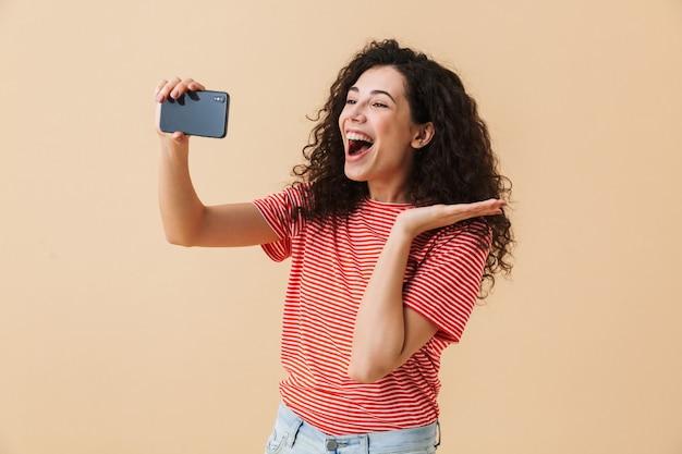 Gelukkig jonge krullende vrouw praten via de mobiele telefoon.