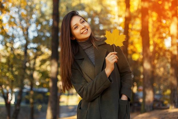 Gelukkig jonge lachende vrouw in een modieuze jas met een gele herfstblad wandelingen in het park bij zonsondergang