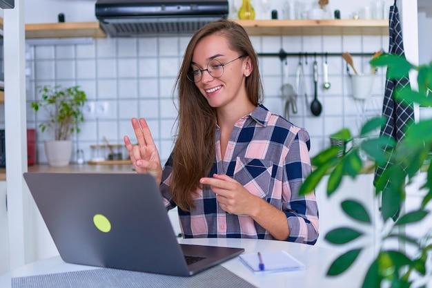 Gelukkig jonge lachende vrouw leren en communiceert in gebarentaal online op een laptop gezellig comfortabel huis