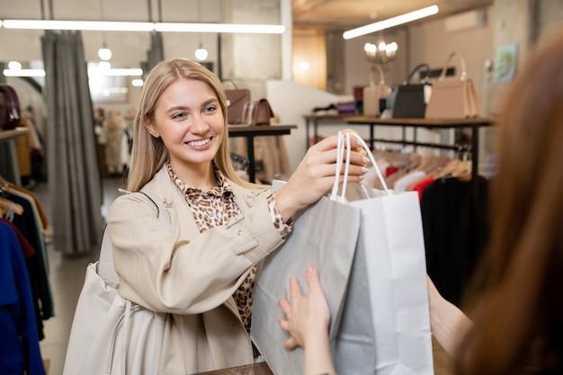 Gelukkig jonge lachende vrouw paperbags met nieuwe kleren doorgeven aan winkelbediende terwijl ze over de toonbank in de boetiek