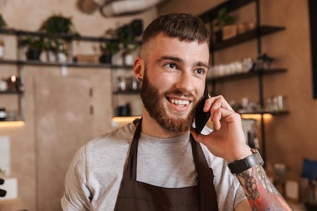 Gelukkig jonge man barista staande in de coffeeshop, praten op mobiele telefoon