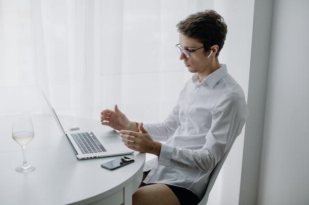 Gelukkig jonge man, bril en lachend, terwijl hij op zijn laptop werkt. man in quarantaine werkt thuis. blijf thuis.