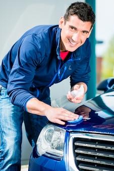 Gelukkig jonge man camera kijken tijdens het waxen van een blauwe auto buiten bij carwash