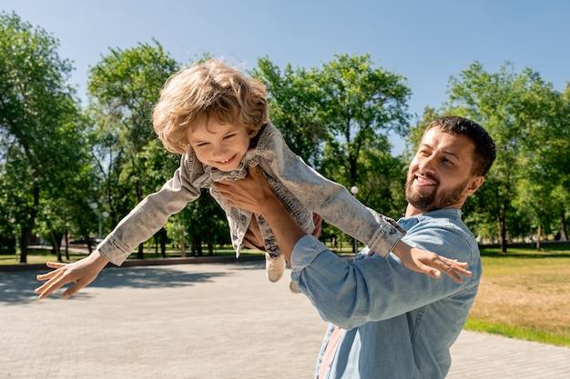 Gelukkig jonge man die zijn schattige vrolijke zoontje vasthoudt, hem optilt en wervelt terwijl hij plezier maakt en geniet van de tijd in het park op een zonnige dag