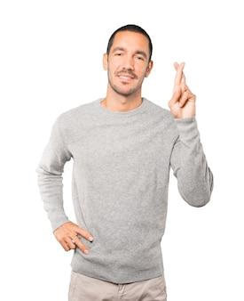 Gelukkig jonge man doet een gebaar van gekruiste vingers
