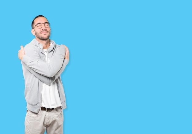 Gelukkig jonge man doet een knuffel gebaar