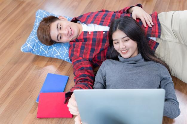 Gelukkig jonge man en mooie vrouw die op de houten vloer liggen en laptop met behulp van