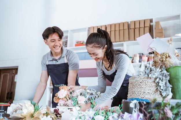 Gelukkig jonge man en vrouw glimlachend praten tijdens het samenwerken in bloemenwinkel