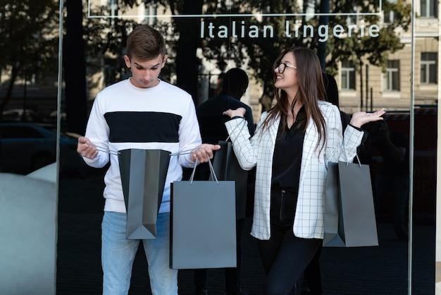 Gelukkig jonge man en vrouw met boodschappentassen. man kijkt verbaasd in de tas. bespotten. zwarte vrijdag.
