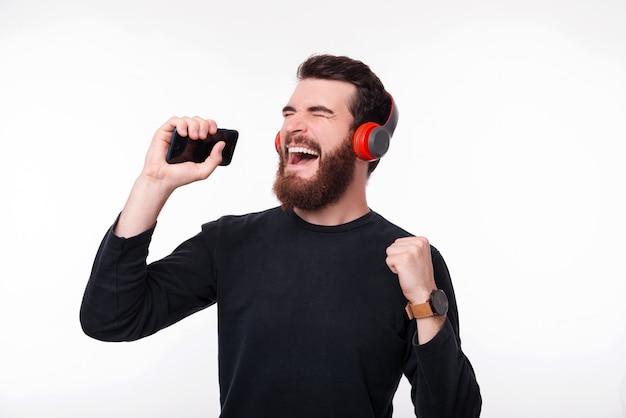 Gelukkig jonge man in casual luisteren muziek op draadloze rode hoofdtelefoon