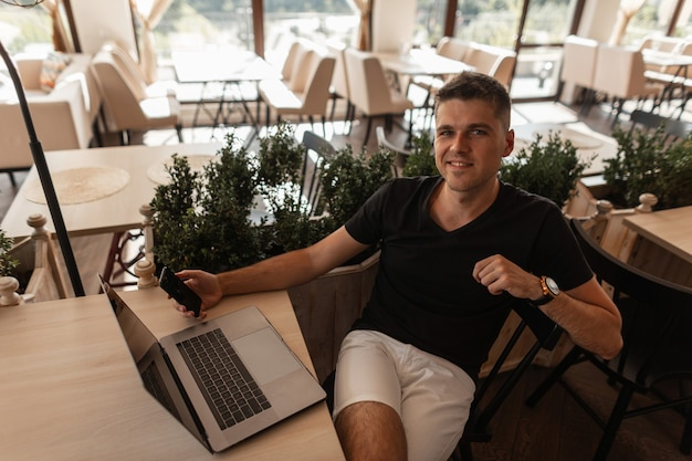 Gelukkig jonge man in een trendy zwart t-shirt rust zittend aan een tafel in een vintage café met een moderne laptop en met een telefoon in handen. succesvolle vrolijke freelancer man ontspant binnenshuis.