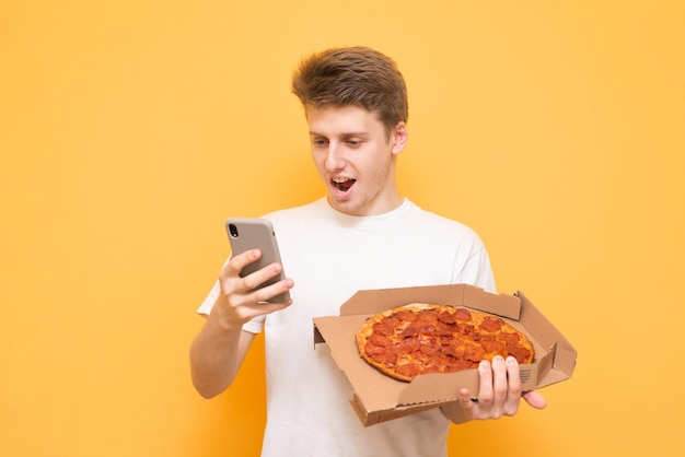 Gelukkig jonge man in een wit t-shirt houdt een doos pizza vast en gebruikt een smartphone op een geel