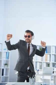 Gelukkig jonge man in formalwear, zonnebril en koptelefoon dansen door werkplek op kantoor tijdens pauze