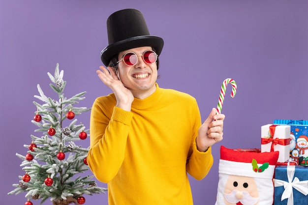 Gelukkig jonge man in gele coltrui en bril met zwarte hoed bedrijf candy cane glimlachend vrolijk permanent naast een kerstboom en presenteert op paarse achtergrond