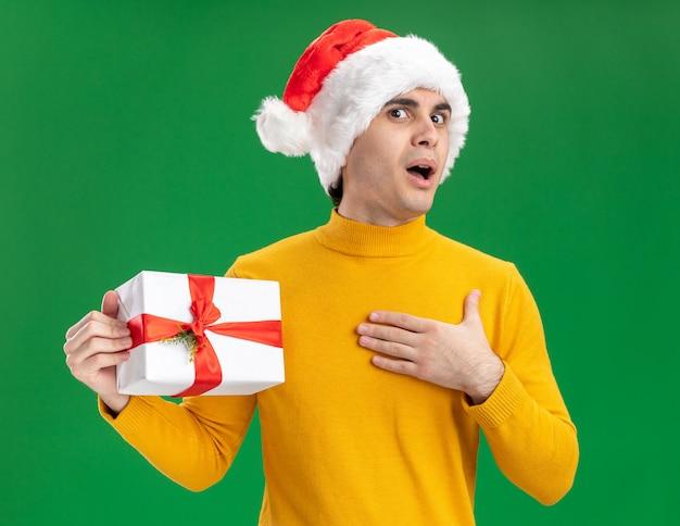 Gelukkig jonge man in gele coltrui en kerstmuts met grappige stropdas met een cadeautje kijken camera verrast staande over groene achtergrond