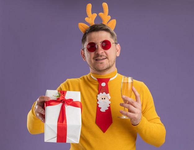 Gelukkig jonge man in gele coltrui en rode bril dragen grappige rode stropdas en rand met herten hoorns glas champagne houden en heden kijken camera glimlachend staande over paarse achtergrond