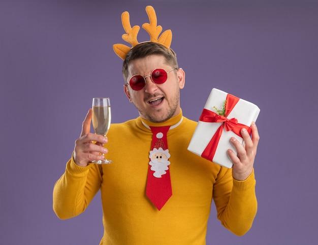 Gelukkig jonge man in gele coltrui en rode bril dragen grappige rode stropdas en rand met herten hoorns glas champagne houden en huidige smling staande over paarse achtergrond