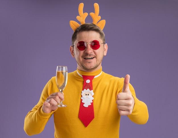 Gelukkig jonge man in gele coltrui en rode bril dragen grappige rode stropdas en rand met herten hoorns houden glas champagne duimen opdagen staande over paarse achtergrond