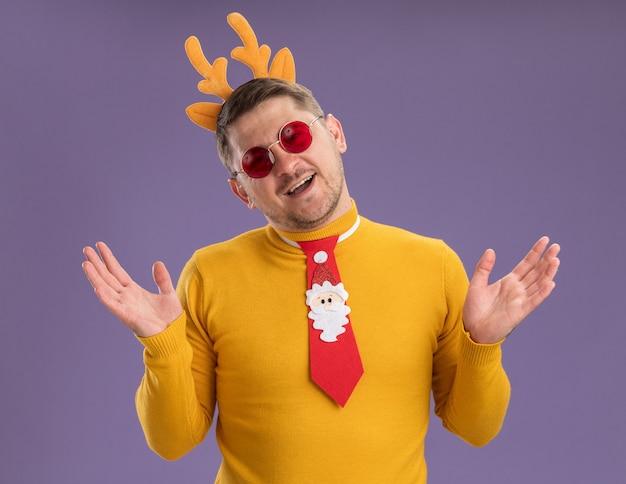 Gelukkig jonge man in gele coltrui en rode bril dragen grappige rode stropdas en rand met herten hoorns kijken camera glimlachend vrolijk met opgeheven armen staande over paarse achtergrond