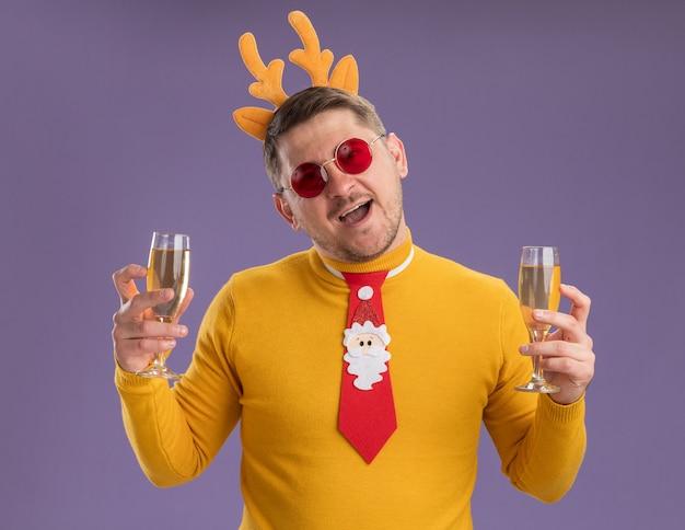 Gelukkig jonge man in gele coltrui en rode bril dragen grappige rode stropdas en rand met herten hoorns met twee glazen champagne met grote glimlach op gezicht staande