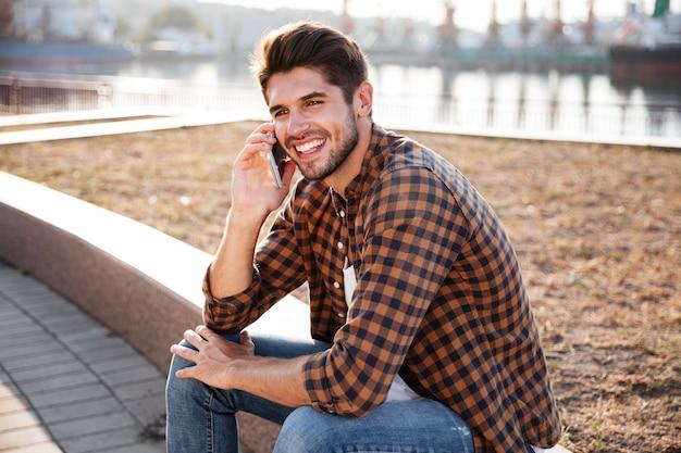 Gelukkig jonge man in geruit hemd zitten en praten op mobiele telefoon in de haven