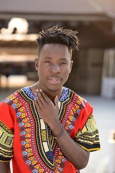 Gelukkig jonge man in nigeriaanse nationale kleding buitenshuis