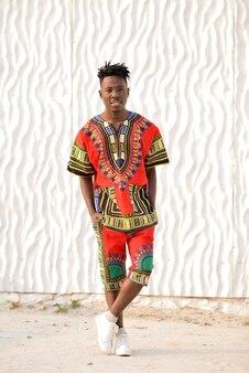 Gelukkig jonge man in nigeriaanse nationale kleding op een witte muur