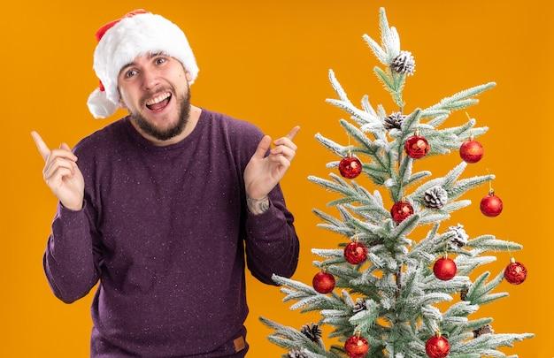 Gelukkig jonge man in paarse trui en kerstmuts camera kijken met glimlach op gezicht met opgeheven armen staande naast kerstboom over oranje achtergrond
