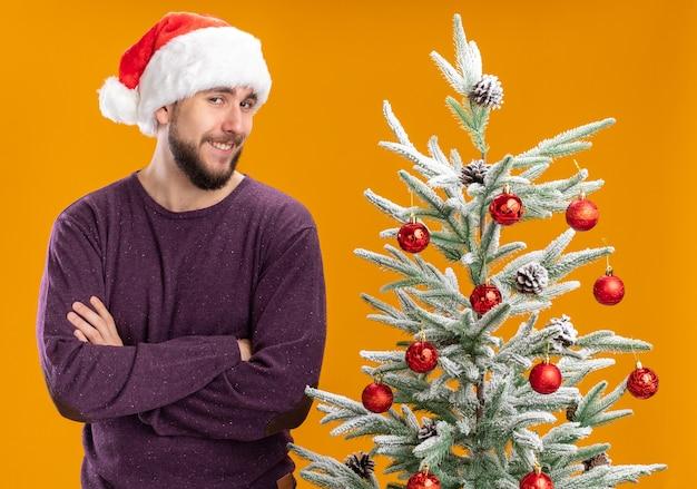 Gelukkig jonge man in paarse trui en kerstmuts kijken camera lacht sluw naast kerstboom over oranje achtergrond