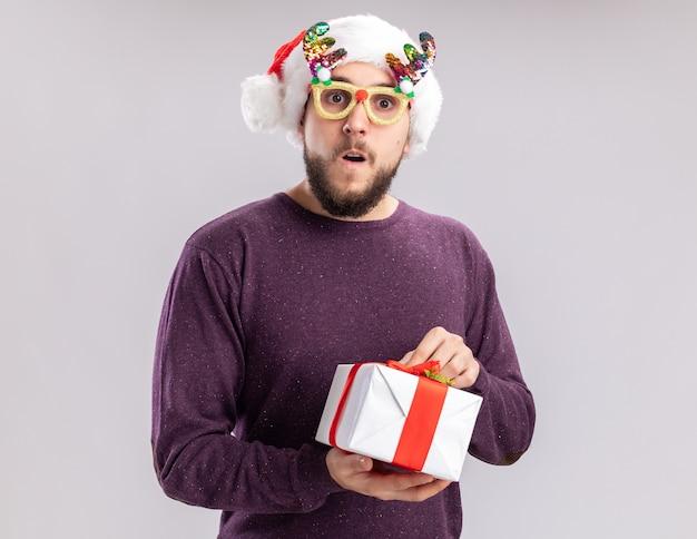 Gelukkig jonge man in paarse trui en kerstmuts met grappige bril met een cadeau kijken camera verrast staande op witte achtergrond