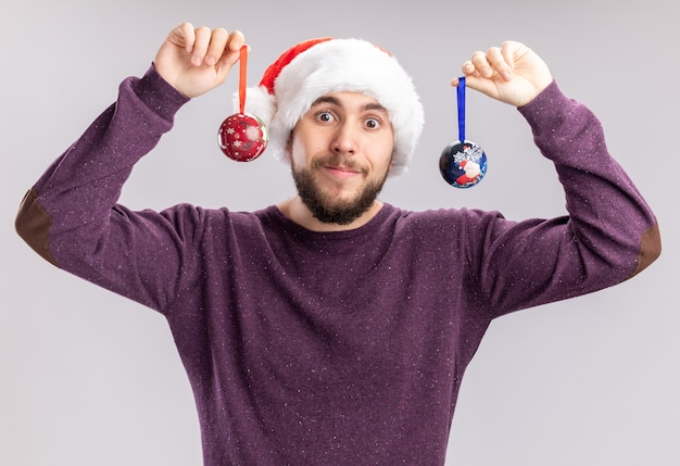 Gelukkig jonge man in paarse trui en kerstmuts met grappige bril met kerstballen kijken camera met glimlach op gezicht permanent op witte achtergrond