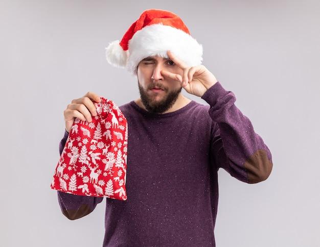 Gelukkig jonge man in paarse trui en kerstmuts met rode tas met geschenken v-teken over zijn oog staande op een witte achtergrond