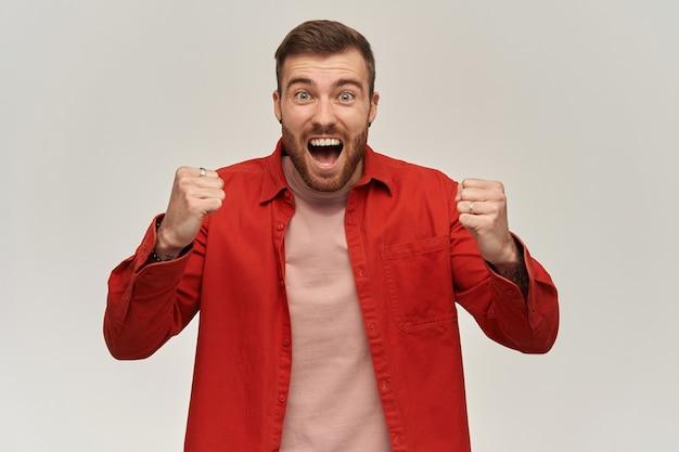 Gelukkig jonge man in rood shirt met baard en geklemd vuisten frontaal kijken en schreeuwen over witte muur succes en viering overwinning concept