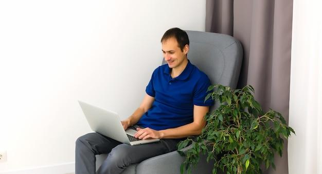 Gelukkig jonge man in t-shirt zittend op de bank thuis, werken op laptop computer, glimlachend.
