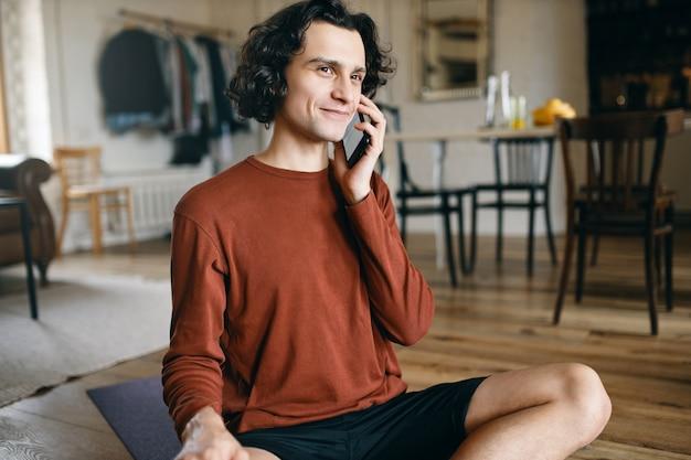 Gelukkig jonge man in vrijetijdskleding de hele dag alleen thuis doorbrengen, terwijl sociale afstand nemen, glimlachend